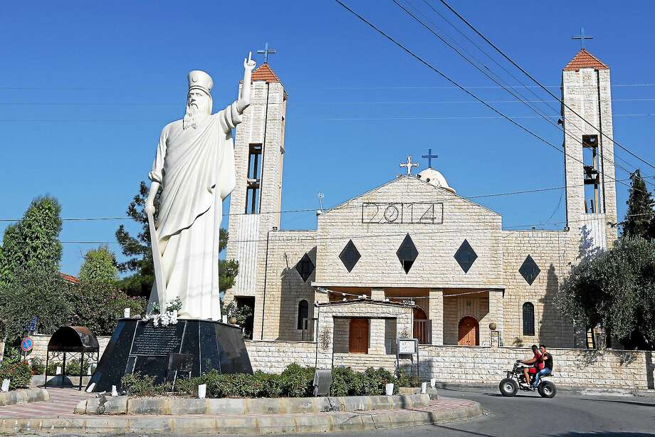 In this Aug. 13, 2014 photo, two young men ride a motorcycle past a church in Lebanon's Christian village of Ras Baalbek in the northern Bekaa region near the border with Syria. Across the Middle East, Christian communities as old as the religion itself feel their very survival is at stake, threatened by militants of the Islamic State group rampaging across Iraq and Syria. Many Christian villagers are setting up self-defense units to protect themselves against attack. Photo: AP Photo/Bilal Hussein  / AP