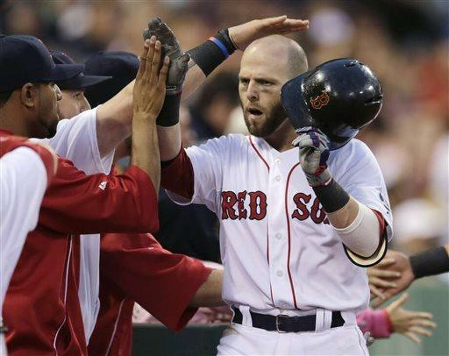 Boston Red Sox's Dustin Pedroia is congratulated by teammates after his two-run home run off Toronto Blue Jays starting pitcher Chien-Ming Wang during the second inning of a baseball game at Fenway Park, Thursday, June 27, 2013, in Boston. (AP Photo/Charles Krupa) Photo: AP / AP