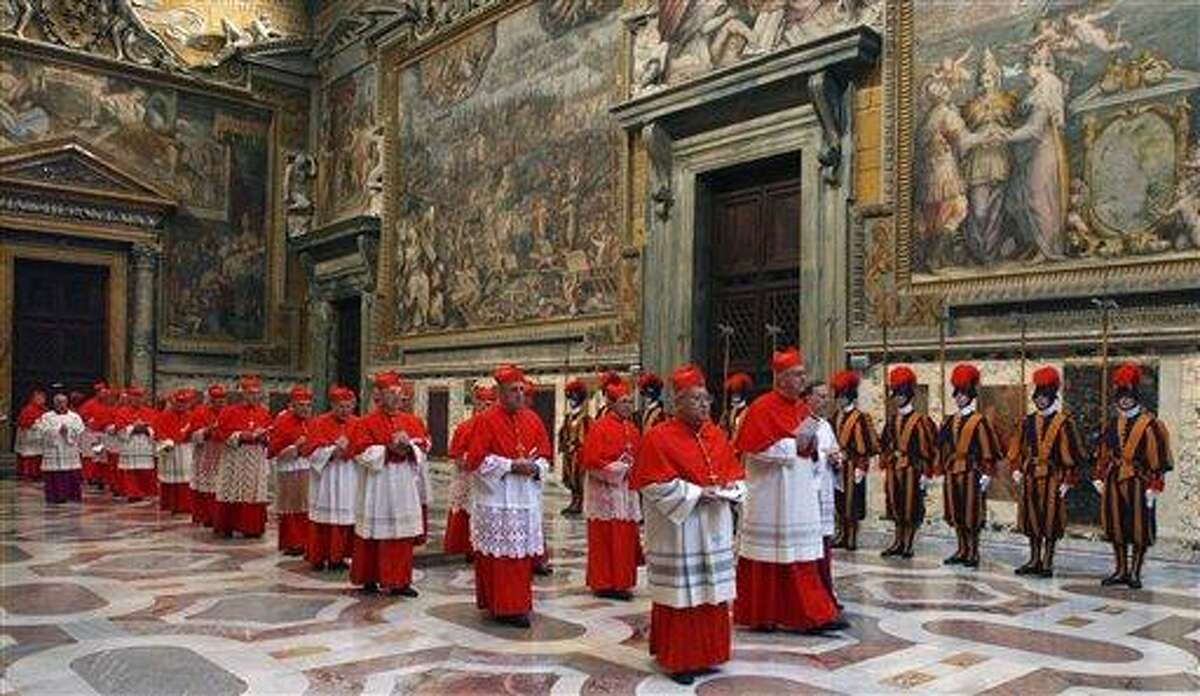 """FILE -- In this photo from files taken on April 18, 2005 and released by the Vatican paper L'Osservatore Romano, Cardinals walk in procession to the Sistine Chapel at the Vatican, at the beginning of the conclave. Next month's conclave to elect the 266th leader of the world's 1.2 billion Catholics will have all the trappings of papal elections past, with the added twist that the this time around the current pope is still very much alive. The conclave begins with the cardinals in their red cassocks processing into the Sistine Chapel, chanting the hypnotic Litany of Saints or Veni Creator imploring the intervention of the Holy Spirit as they take their places before Michelangelo's """"Last Judgment."""" (AP Photo/Osservatore Romano, ho)"""