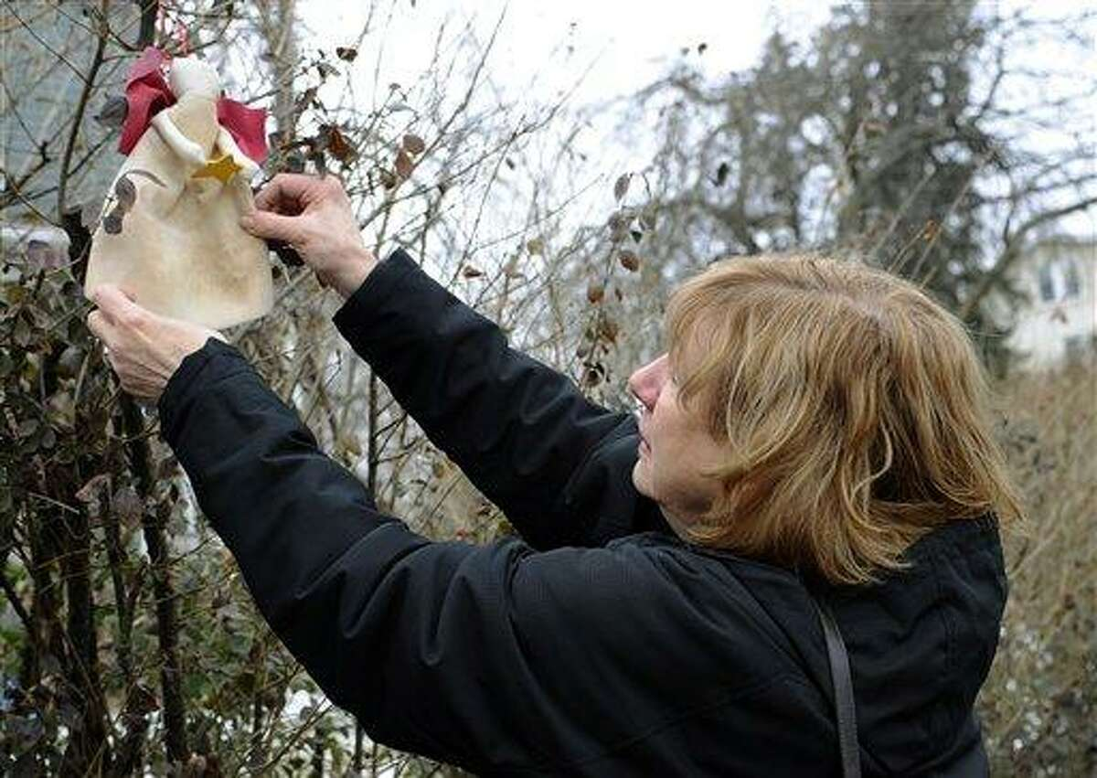In this Tuesday, Feb. 5, 2013 photo, Teresa Rousseau, mother of Sandy Hook Elementary School victim Lauren Rousseau, straightens out a sewn angel left in a bush by a stranger outside her home in Danbury, Conn. Teacher Lauren Rousseau, 30, was one of 26 people killed in the Dec. 14, 2012 massacre at Sandy Hook Elementary School in Newtown, Conn. Lauren Rousseau will be one of six educators from the school honored posthumously with the 2012 Presidential Citizens Medal, presented at a White House ceremony on Feb. 15. (AP Photo/Jessica Hill)