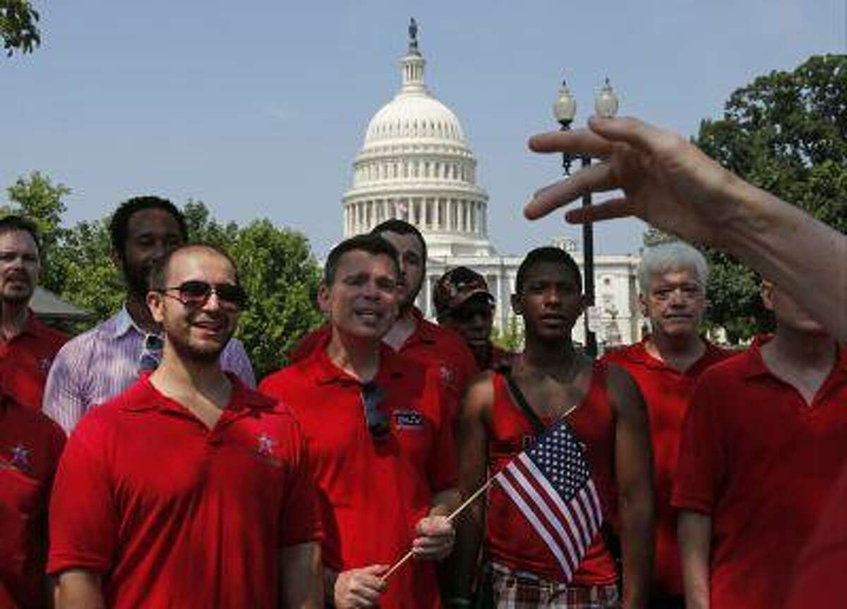 With the Capitol in the background, the Gay Men's Choir of Washington, D.C. performs in front of the Supreme Court in Washington, Wednesday, June 26, 2013. In a major victory for gay rights, the Supreme Court on Wednesday struck down a provision of a federal law denying federal benefits to married gay couples and cleared the way for the resumption of same-sex marriage in California. (AP Photo/Charles Dharapak)