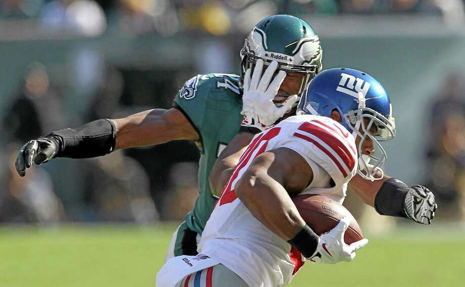 The Giants' Victor Cruz runs the ball against the defense of Eagles' Bradley Fletcher during first half of Sunday's game. Photo: Yong Kim — The Associated Press/Philadelphia Daily News  / Philadelphia Daily News