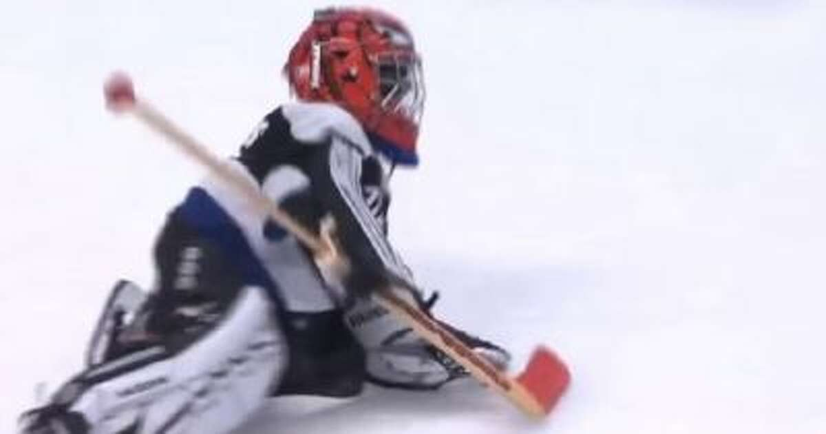 A youth hockey goalie works his way across the ice during an intermission at an NHL game.
