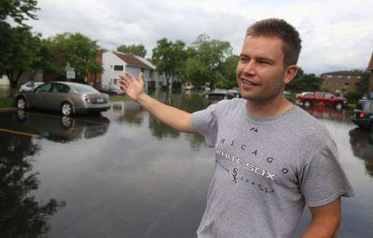 Greg Mandrek describes the damage to his cars and apartment after flooding at the Runaway Bay Apartments in Palatine, Ill. on Wednesday June 26, 2013.