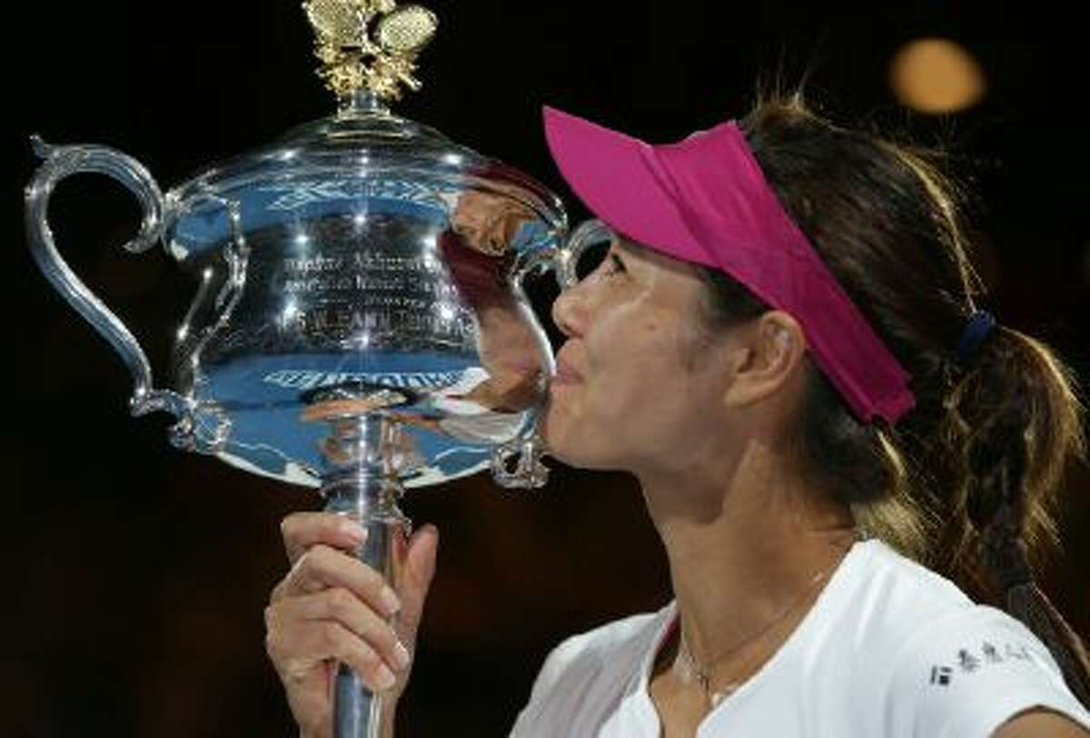 Li Na of China kisses the championship trophy after defeating Dominika Cibulkova of Slovakia in their women's singles final at the Australian Open Saturday.
