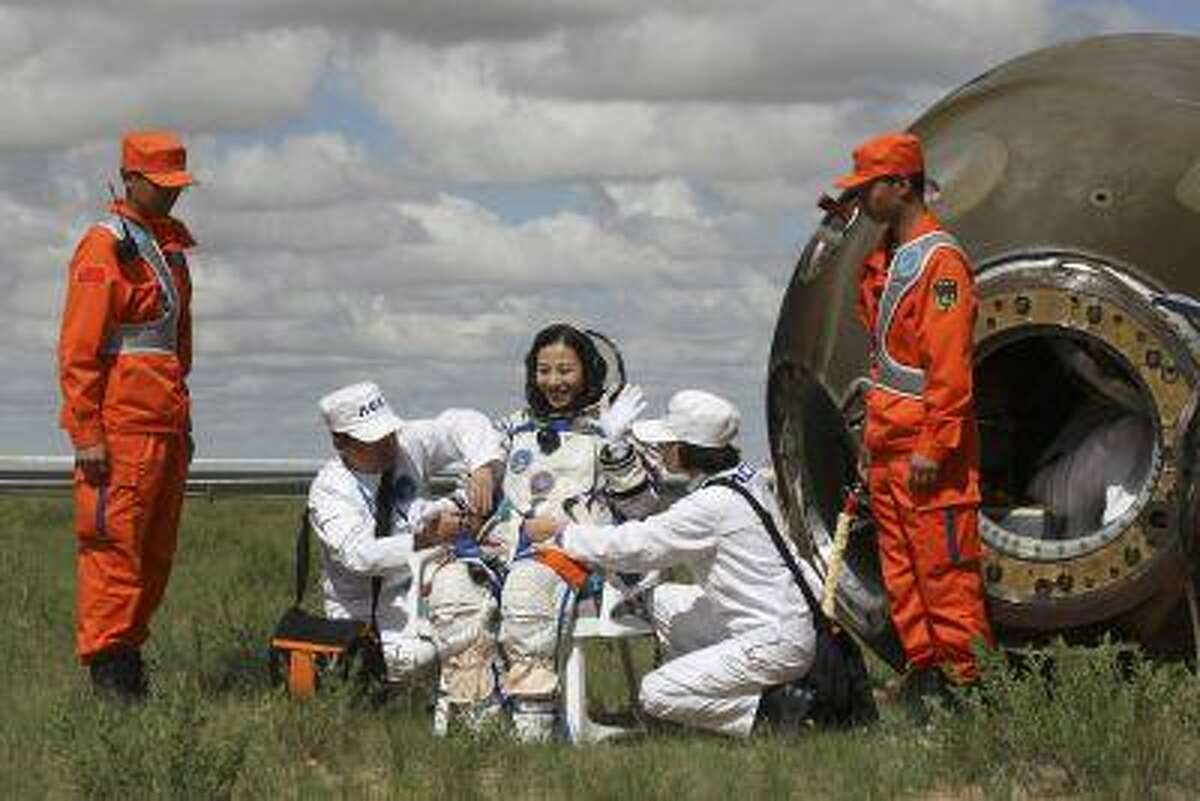 Chinese astronaut Wang Yaping waves after she gets out from the re-entry capsule of China's Shenzhou-10 spacecraft returning to earth at its main landing site in north China's Inner Mongolia Autonomous Region, June 26, 2013.