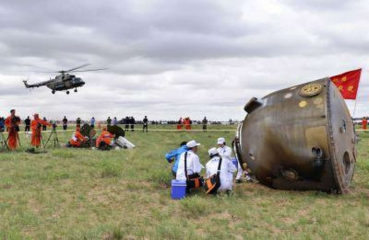 Ground crew helps a Chinese astronaut exit from the re-entry capsule of China's Shenzhou-10 spacecraft after it returning to earth at its main landing site in north China's Inner Mongolia Autonomous Region, June 26, 2013.