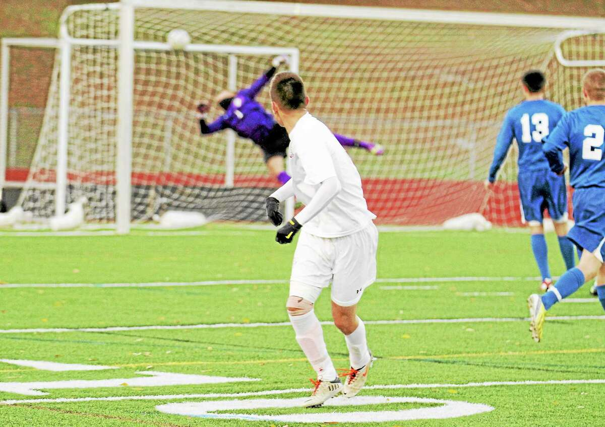 Torrington's Amar Suljic scores as St. Paul goalkeeper jumps in an attempt to make a save.