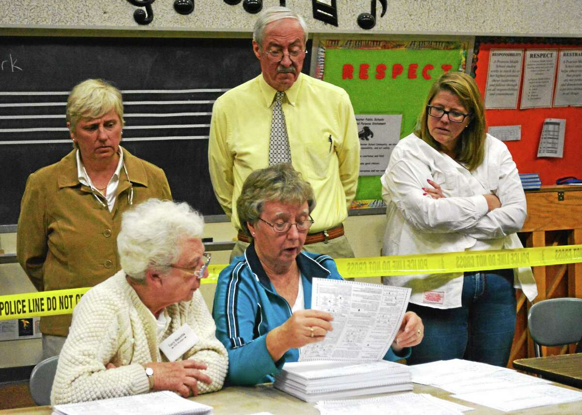 Selectmen Candy Perez, Steve Sedlack and Marsha Sterling look on as Lucy Bascetta and Sally Mangione hand-count the votes from Saturday's special election.