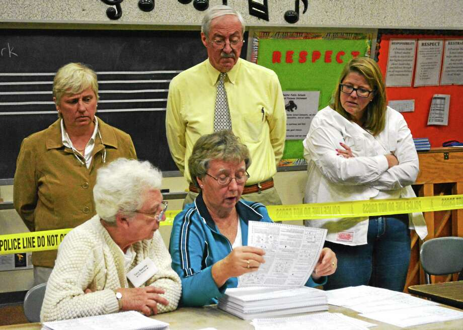 Selectmen Candy Perez, Steve Sedlack and Marsha Sterling look on as Lucy Bascetta and Sally Mangione hand-count the votes from Saturday's special election. Photo: Ryan Flynn — The Register Citizen