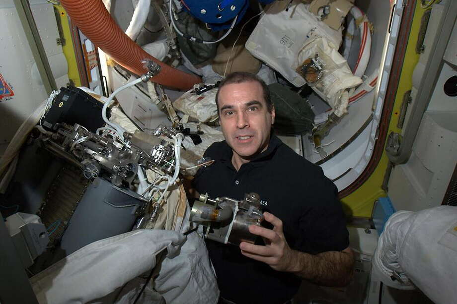 In this photo provided by NASA, astronaut Rick Mastracchio works to replace a pump in a spacesuit, Monday, April 14, 2014, aboard the International Space Station. SpaceX called off a launch to the space station on Monday, April 14, 2014, because of a rocket leak. Officials said they believe the problem can be fixed by Friday, the next opportunity for flying and the last chance before astronauts do urgent spacewalking repairs. (AP Photo/NASA) Photo: AP / NASA