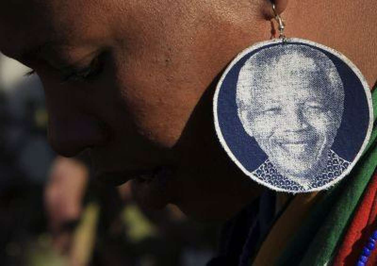 An unidentified woman wearing earrings bearing the image of former South African President Nelson Mandela, outside the Mediclinic Heart Hospital where he is being treated in Pretoria, South Africa, Wednesday, June 26, 2013.