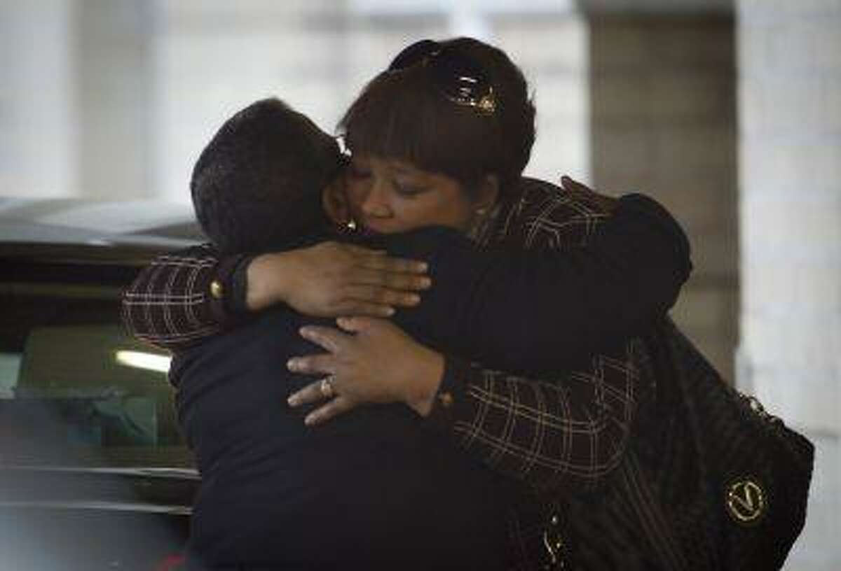 Daughter Zindzi Mandela, right, receives a hug from an unidentified woman, left, as she arrives at the Mediclinic Heart Hospital where former South African President Nelson Mandela is being treated in Pretoria, South Africa Wednesday, June 26, 2013.