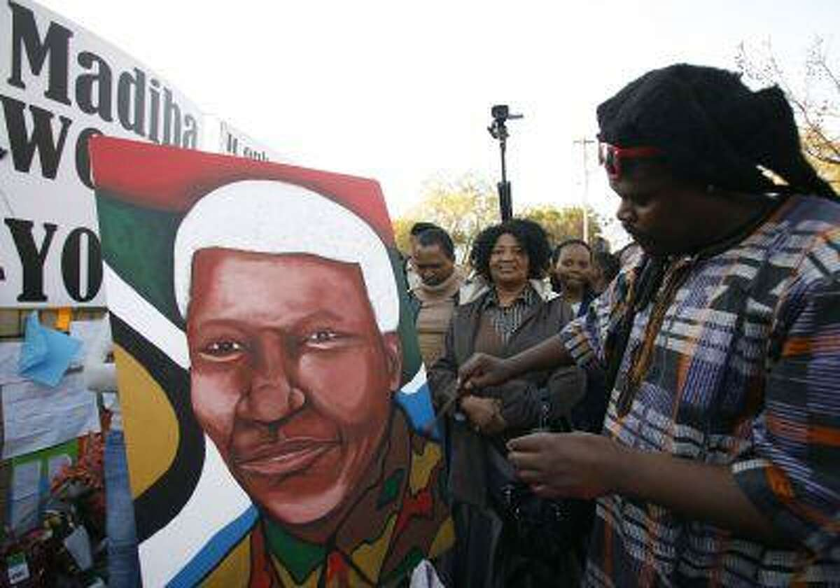 Lebani Sirinje, a Zimbabwean artist paints a portrait of former South African President Nelson Mandela, outside the Mediclinic Heart Hospital where is being treated in Pretoria, South Africa Wednesday, June 26, 2013.