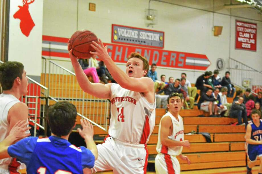 Northwestern's John Lippincott lays in two of his 11 points in the Highlanders 61-57 overtime win against Nonnewaug. Photo: Pete Paguaga — Register Citizen