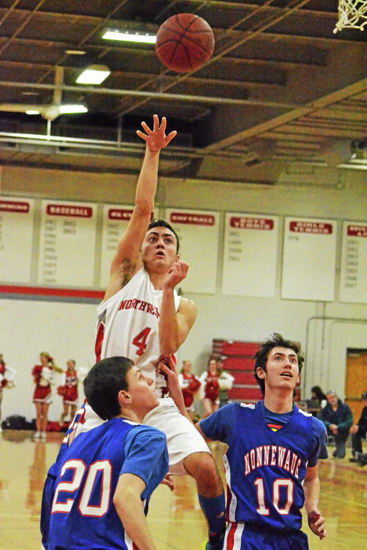 Northwestern's Zach Tuxbury floats his shot over Nonnewaug's Dan Ecesdy for two of his 13 points the Highlanders 61-57 overtime win against the Chiefs.