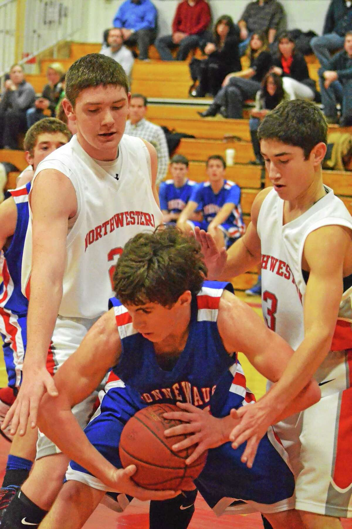 Northwestern's Steven McGrath (left) and Rich Persechino (right) trap Nonnewaug's Ryan Gunnoud during the Highlanders 61-57 overtime win.