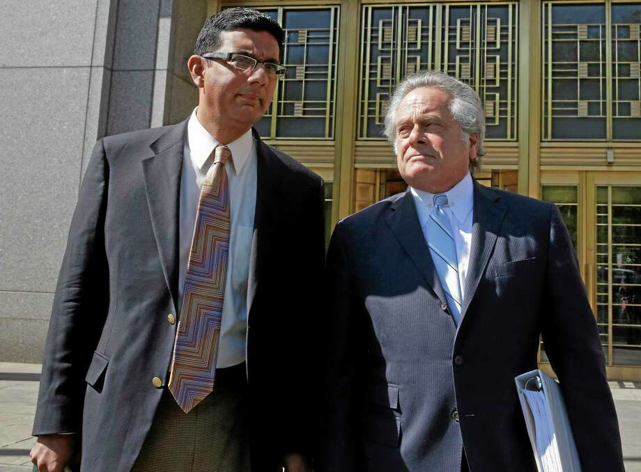 Conservative scholar and filmmaker Dinesh D'Souza, left, accompanied by his lawyer Benjamin Brafman leave federal court, in New York,  Tuesday, May 20, 2014.  D'Souza has pleaded guilty in New York federal court to making illegal campaign contributions. He admitted getting two close associates to make $10,000 contributions to Wendy Long. She was a candidate who lost the New York Senate race in 2012 to the Democratic incumbent. His plea agreement calls for a sentence of 10 to 16 months in prison. He'll be sentenced on Sept. 23. (AP Photo/Richard Drew) Photo: AP / AP