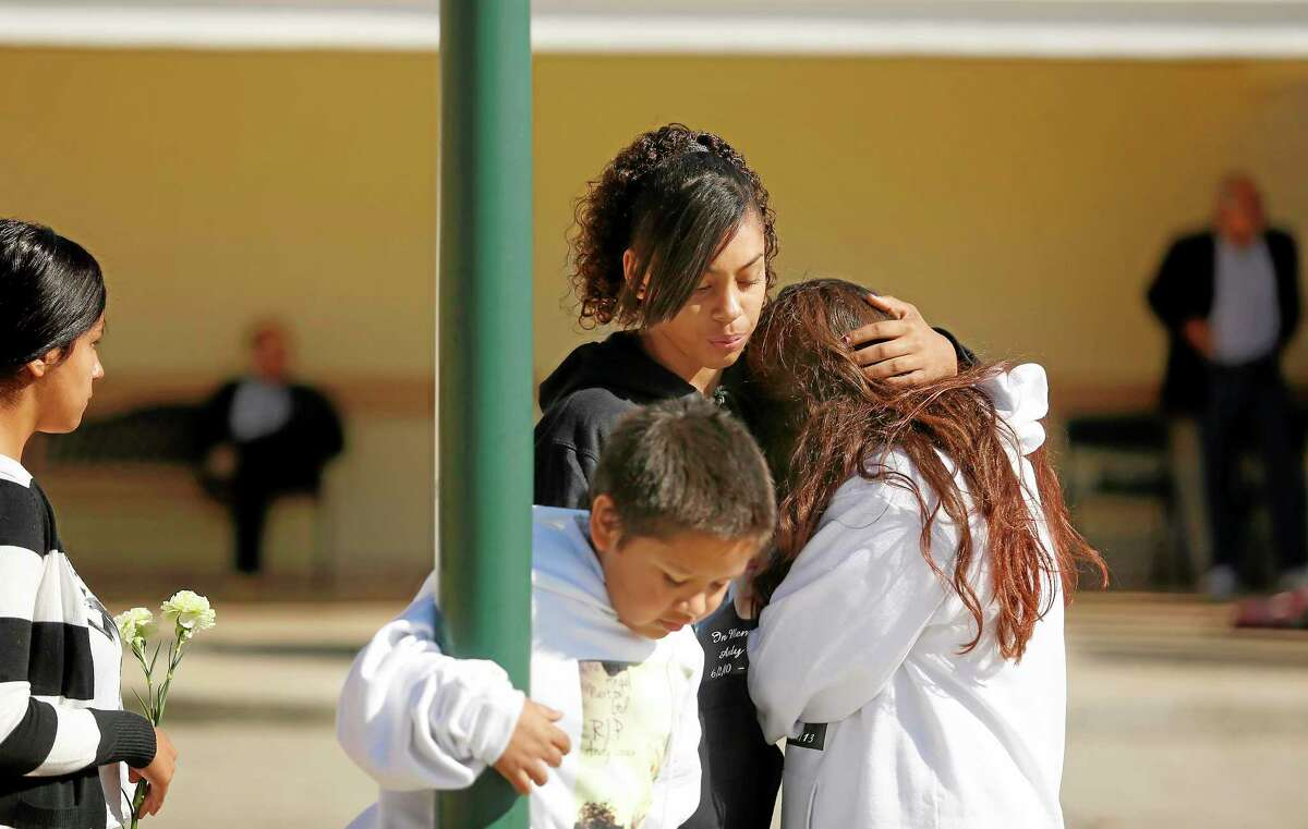 Mariah Burrham consoles her friend Aliyah Martinez during the memorial service and viewing of Andy Lopez at the Windsor-Healdsburg Mortuary on Sunday, Oct. 27, 2013. (AP Photo/The Press Democrat, Conner Jay)