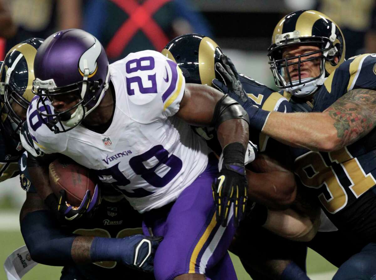 Minnesota Vikings running back Adrian Peterson runs for a 5-yard gain as Rams defensive end Chris Long defends during a Sept. 7 game in St. Louis.
