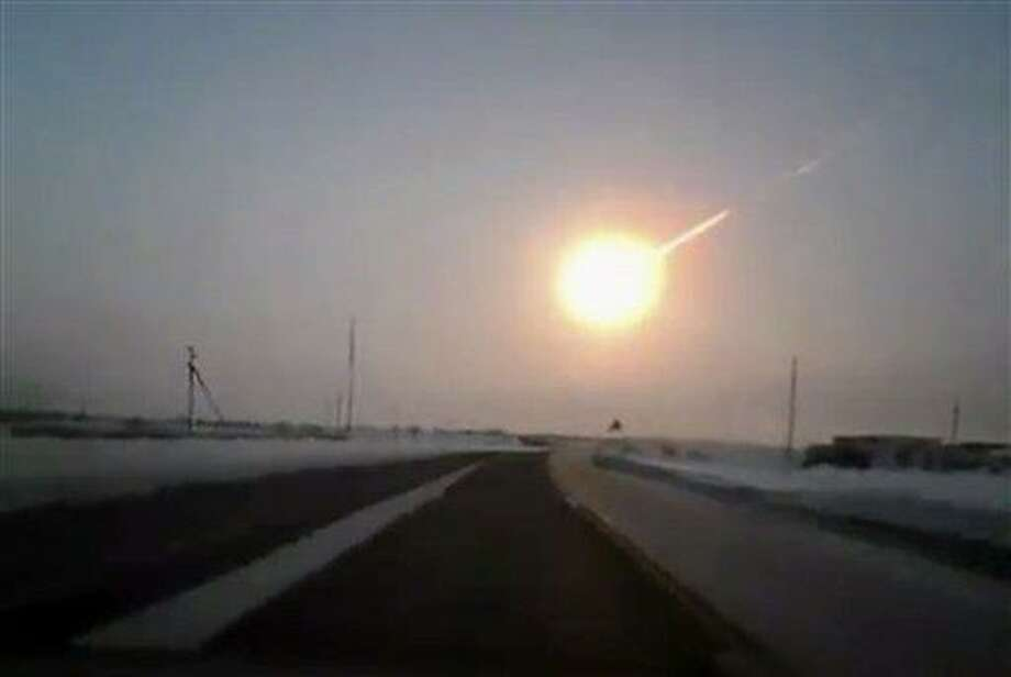 """In this frame grab made from a video, on a highway from Kostanai, Kazakhstan, to Chelyabinsk region, Russia, provided by Nasha Gazeta newspaper, on Friday, Feb. 15, 2013 a meteorite contrail is seen. A meteor streaked across the sky of Russia's Ural Mountains on Friday morning, causing sharp explosions and reportedly injuring around 100 people, including many hurt by broken glass. (AP Photo/Nasha gazeta, <a href=""""http://www.ng.kz"""">www.ng.kz</a>) Photo: AP / www.ng.kz"""