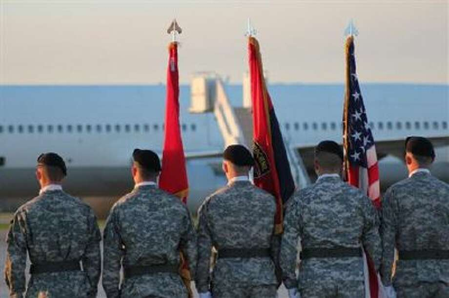 """An honor guard from the 101st Airborne Division at Fort Campbell, Ky., waits on the tarmac Wednesday for 140 soldiers from the 4th Brigade Combat Team, also known as the Currahees, to depart a plane after six months in Afghanistan. The fabled unit, chronicled in a book and HBO miniseries """"Band of Brothers,"""" is being inactivated this spring as part of the U.S. Army's efforts to shrink the size of its fighting force. (AP Photo/Brett Barrouquere) Photo: AP / AP"""