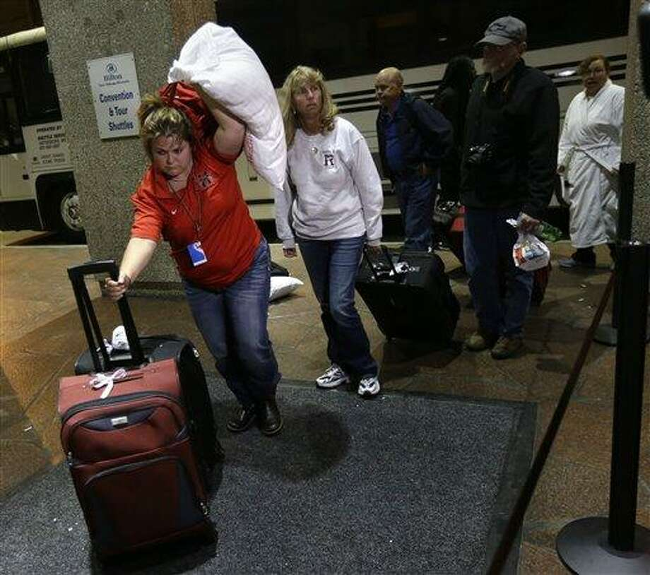 Passengers from the disabled Carnival Triumph cruise ship arrive by bus at the Hilton Riverside Hotel in New Orleans, Friday, Feb. 15, 2013.  The ship had been idled for nearly a week in the Gulf of Mexico following an engine room fire. (AP Photo/Gerald Herbert) Photo: AP / AP