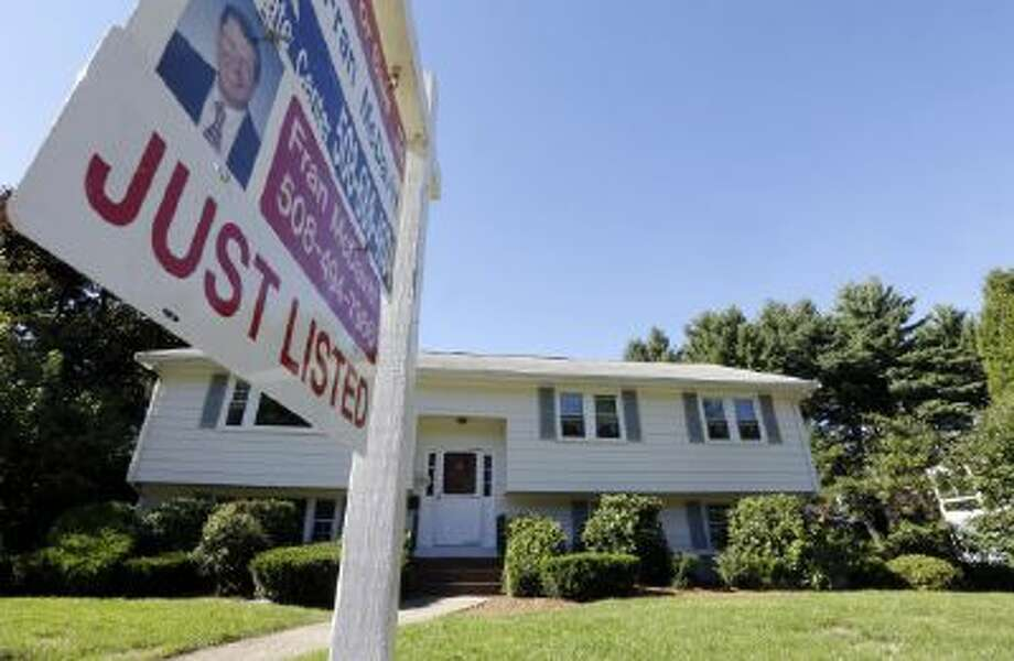 In this Wednesday, Sept. 18, 2013 photo, a for sale sign hangs in front of a house in Walpole, Mass.