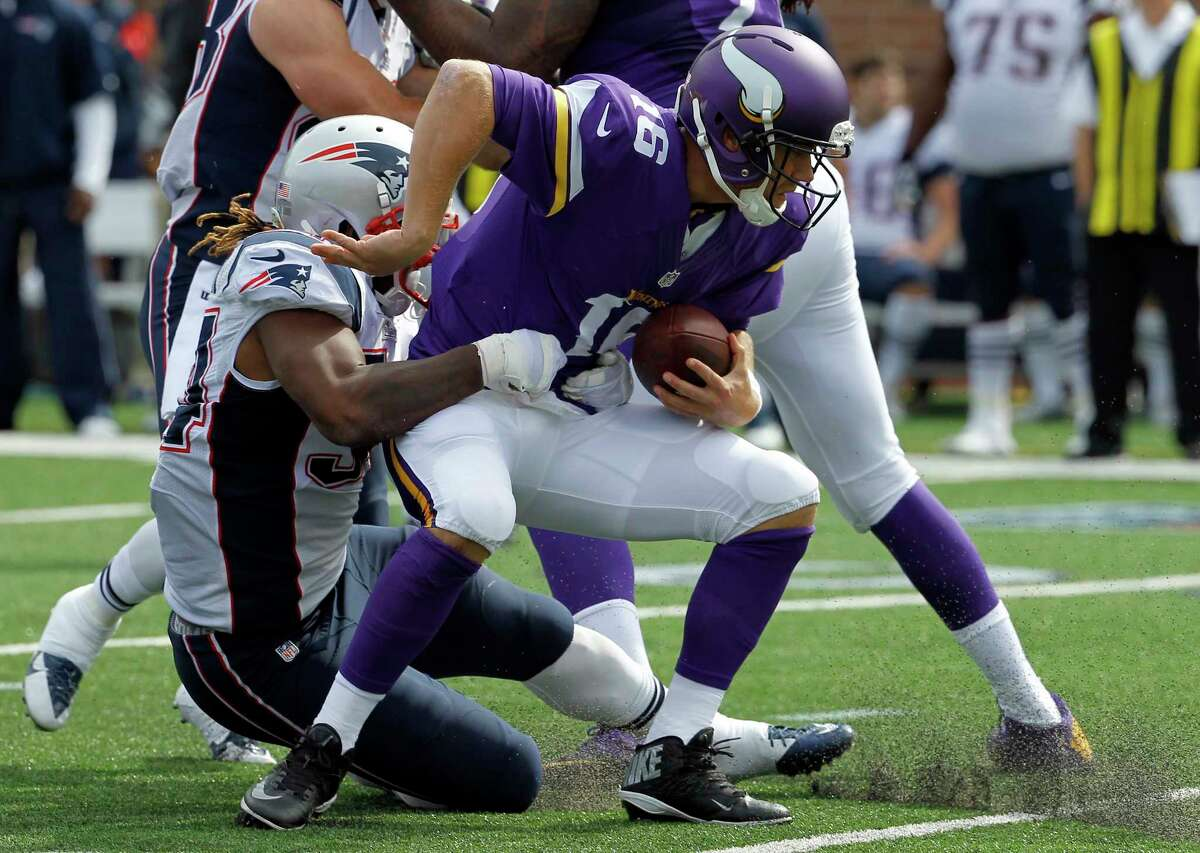 Minnesota Vikings quarterback Matt Cassel, right, is sacked for an 8-yard loss by New England Patriots linebacker Dont'a Hightower during the third quarter of Sunday's game in Minneapolis.