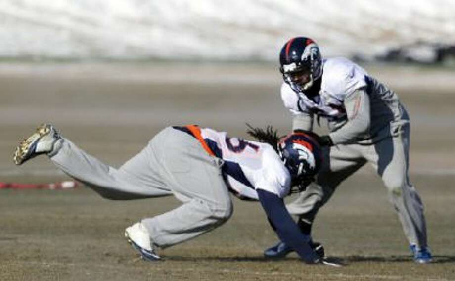 Denver Broncos outside linebacker Nate Irving, left, and middle linebacker Paris Lenon (51) work on a drill during a Thursday practice in Englewood, Colo.