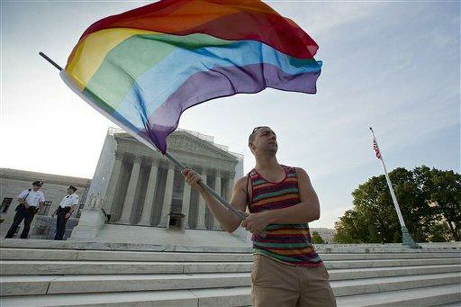 Gay rights advocate Vin Testa waves a rainbow flag in front of the Supreme Court at sun up in Washington, Wednesday, June 26, 2013. Justices are expected to hand down major rulings on two gay marriage cases that could impact same-sex couples across the country. One is a challenge to California's voter-enacted ban on same-sex marriage. The other is a challenge to a provision of federal law that prevents legally married gay couples from receiving a range of tax, health and pension benefits.   (AP Photo/J. Scott Applewhite) Photo: AP / AP