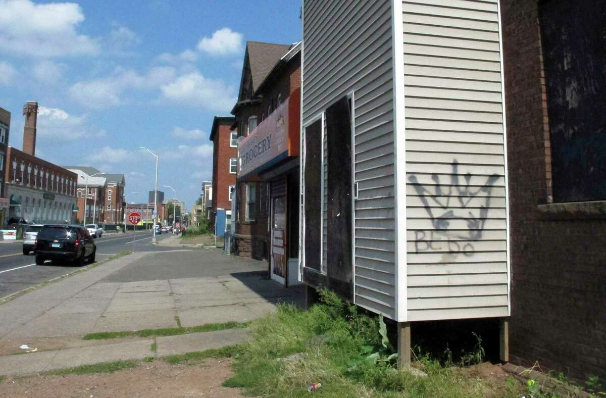 In this Sept. 5, 2014 photo, Latin Kings gang graffiti decorates a building in Hartford. While gangs still mark their territory with graffiti, police said many members have shied away from wearing their colors in an effort to avoid being detected by authorities.