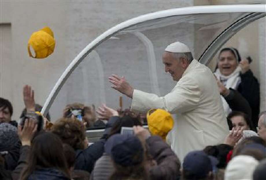 A cap is thrown toward Pope Francis as he arrives Wednesday in his pope-moblie for his weekly general audience in St. Peter's Square at the Vatican. Photo: AP / AP