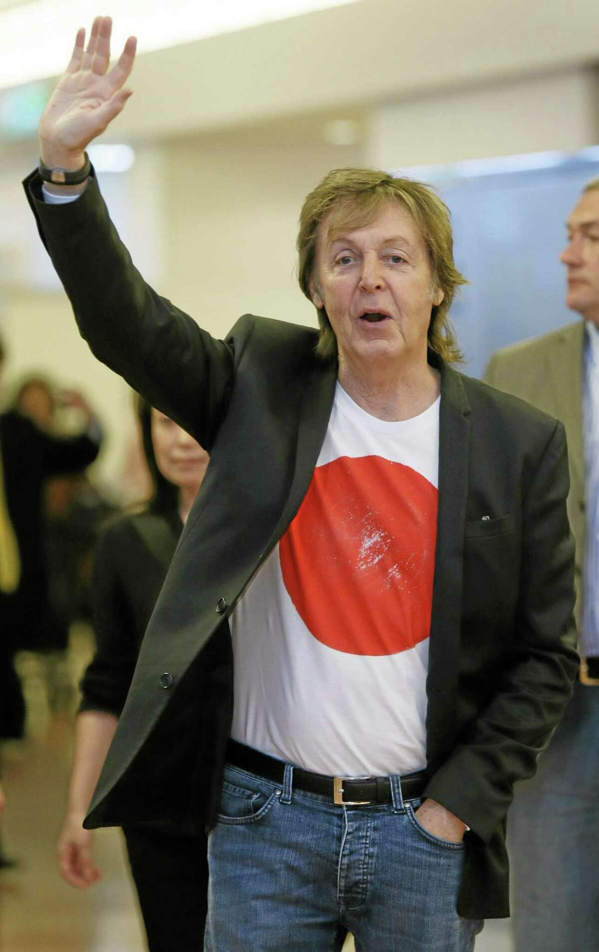 In this Thursday, May 15, 2014 photo, Paul McCartney waves upon arrival at Haneda international airport in Tokyo. (AP Photo/Kyodo News)