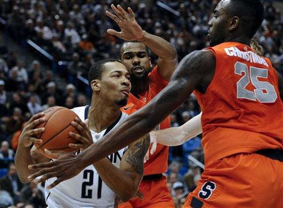 Connecticut's Omar Calhoun, left, is pressured by Syracuse's James Southerland, center, and Syracuse's Rakeem Christmas, right, during the second half of an NCAA college basketball game in Hartford, Conn., Wednesday, Feb. 13, 2013. Connecticut won 66-58. (AP Photo/Jessica Hill) Photo: ASSOCIATED PRESS / A2013