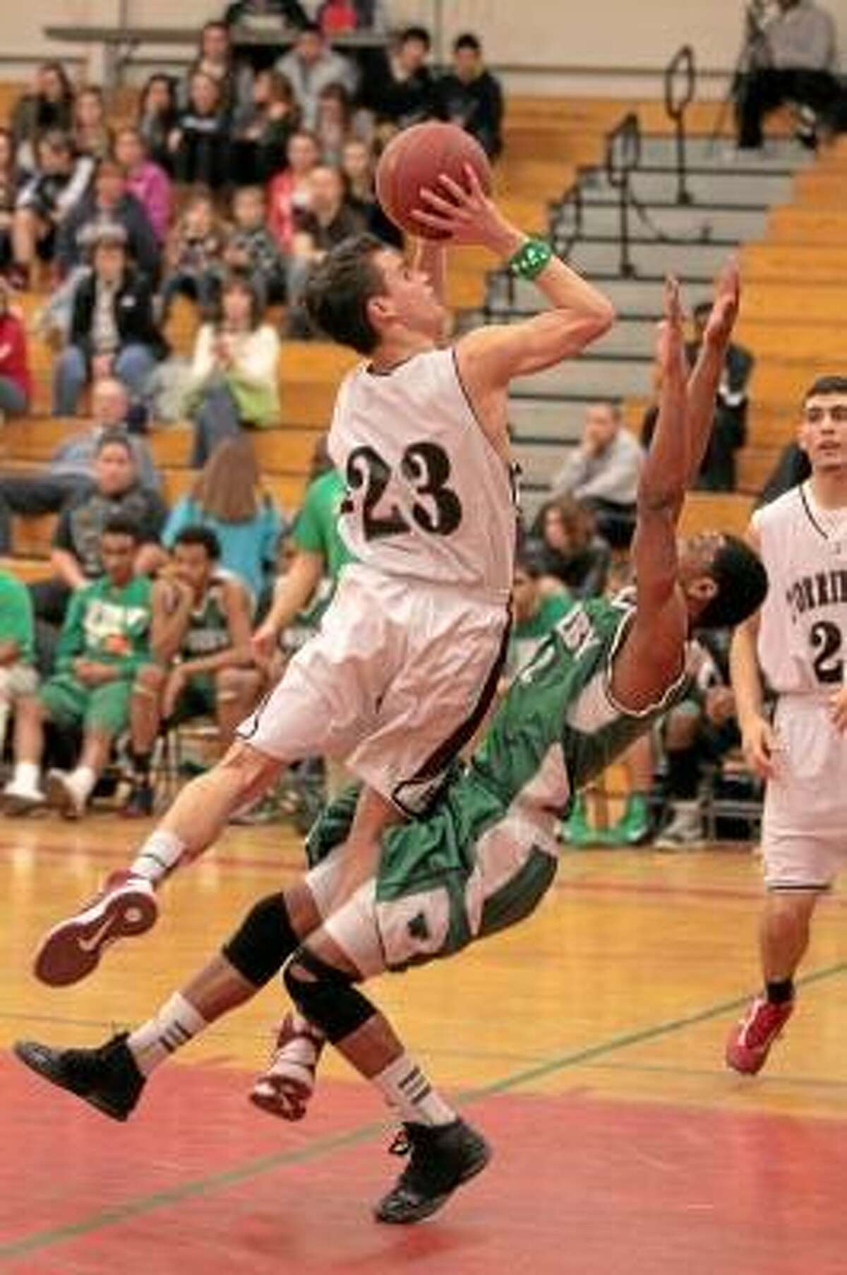 Torrington's Austin Kelson (23) collides with a Wilby defender as he goes for a layup. Marianne Killackey/Special to Register Citizen.