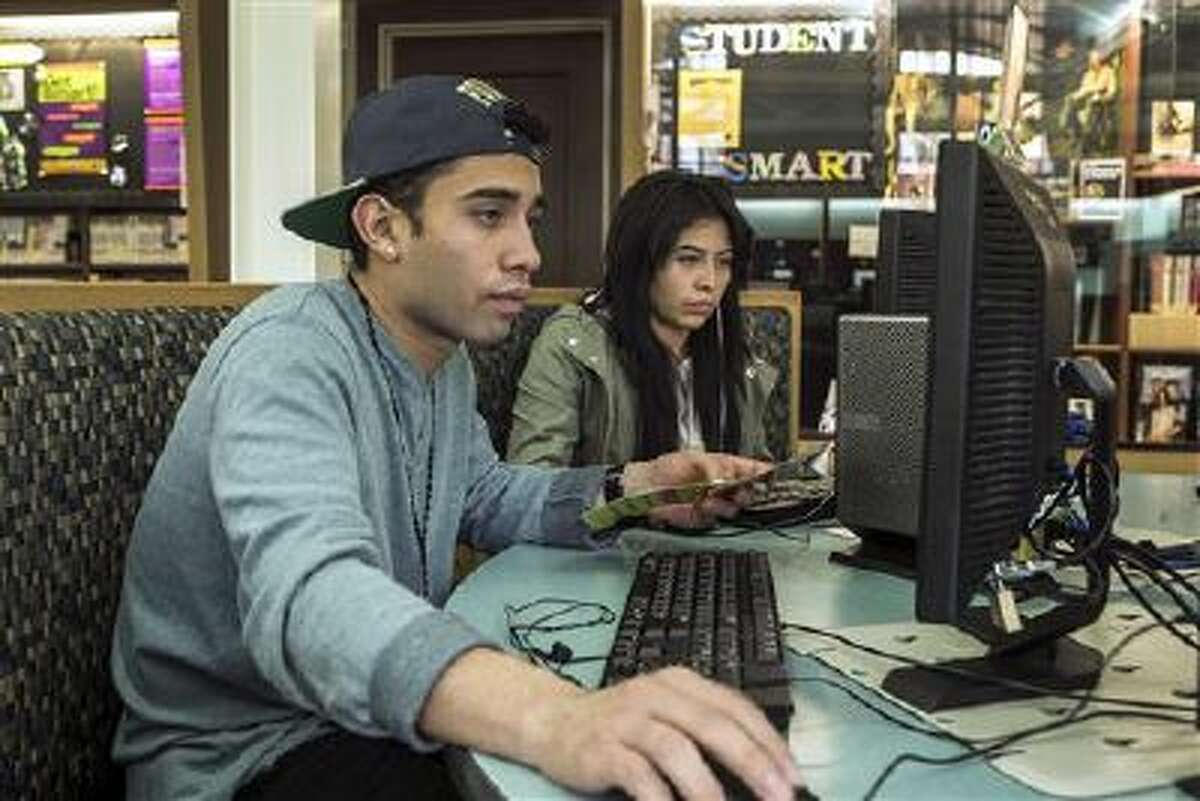 19-year-olds Alexander Alegria and Michelle Rivera use computers to access the Internet at the Teen'Scape area at the Los Angeles Public Library in Los Angeles.