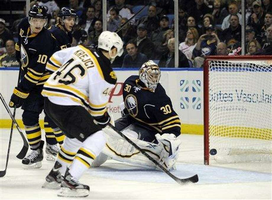 Boston Bruins center David Krejci, (46), of the Czech Republic, watches the puck hit the goalpost as Buffalo Sabres defenseman Christian Ehrhoff (10), of Germany, and goaltender Ryan Miller (30) react during the second period of an NHL hockey game in Buffalo, N.Y., Friday, Feb. 15, 2013. (AP Photo/Gary Wiepert) Photo: ASSOCIATED PRESS / AP2013