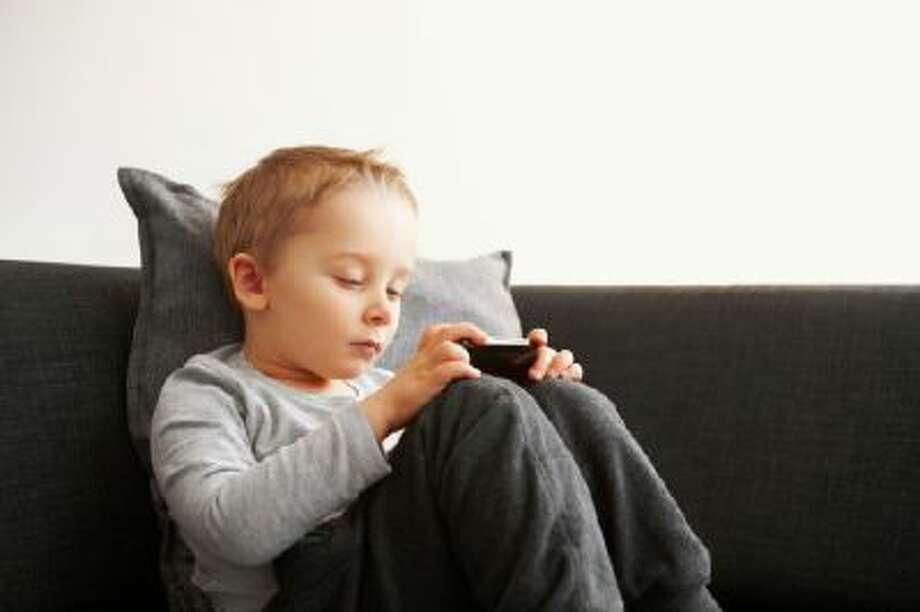Innocent little kid using mobile phone Photo: Getty Images/Vetta / Vetta