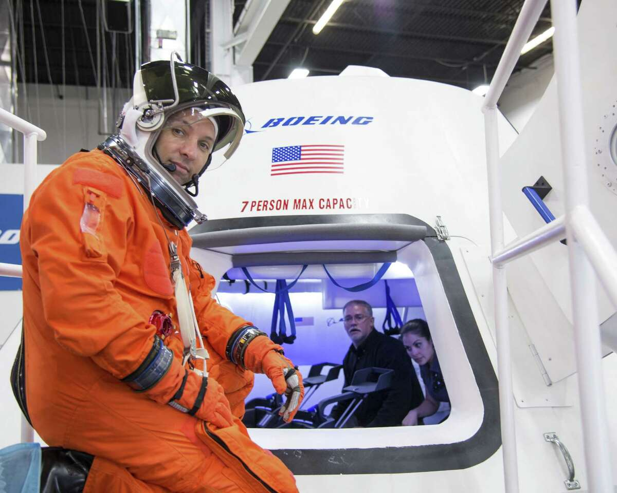 In this undated image provided by NASA, astronaut Randy Bresnik prepares to enter The Boeing Company's CST-100 spacecraft for a fit check evaluation at the company's Houston Product Support Center. (AP Photo/NASA)