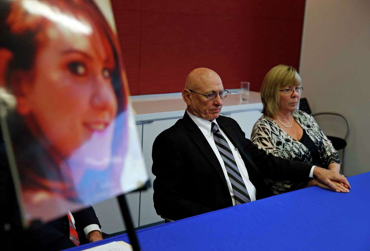 Lonnie and Sandy Phillips listen as their lawyer speaks during a news conference on Tuesday, Sept. 16, 2014. The Phillips, parents of Jessica Ghawi, who was killed in the July 20, 2012 Colorado theater shootings, filed a lawsuit Tuesday accusing four online retailers of improperly selling ammunition, tear gas, a high-capacity magazine and body armor used in the attack. (AP Photo/Brennan Linsley)