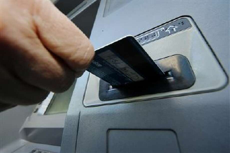 In this Saturday, Jan. 5, 2013 photo, a person demonstrates using a credit card in an ATM machine in Pittsburgh. ricans stepped up borrowing in January to buy cars and attend school, while staying cautious about using their credit cards. (AP Photo/Gene J. Puskar) Photo: ASSOCIATED PRESS / AP2013