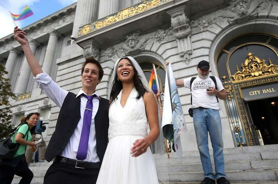 Lisa Dazols, left, and her partner of five years Jenni Chang, of San Francisco, celebrate the Supreme Court's decision on Proposition 8 and the Defense of Marriage Act after a screening at City Hall in San Francisco, Calif., on Wednesday, June 26, 2013. The U.S. Supreme Court dismissed California's Proposition 8 and declared the 1996 Defense of Marriage Act unconstitutional. (Jane Tyska/Bay Area News Group) Photo: JANE TYSKA / THE OAKLAND TRIBUNE/BAY AREA NEWS GROUP EAST BAY/MEDIA NEWS GROUP/DIGITAL FIRST MEDIA