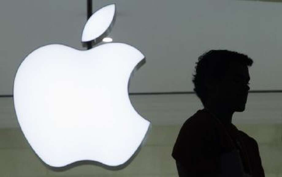 In this Dec. 7, 2011 file photo, a person stands near the Apple logo at the company's new store in Grand Central Terminal, in New York.
