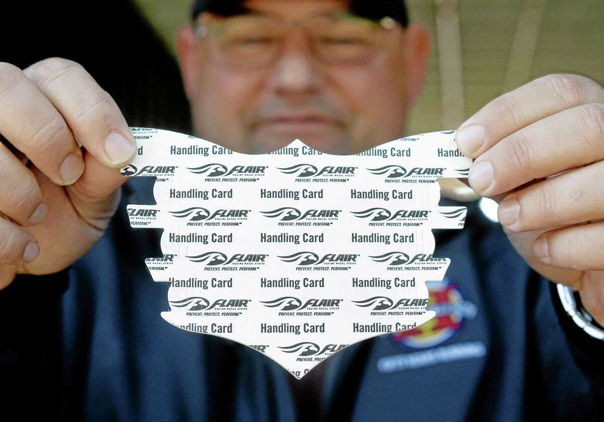Alan Sherman, assistant trainer for Kentucky Derby and Preakness winner California Chrome, displays a nasal strip at Pimlico Race Course in Baltimore on Monday.