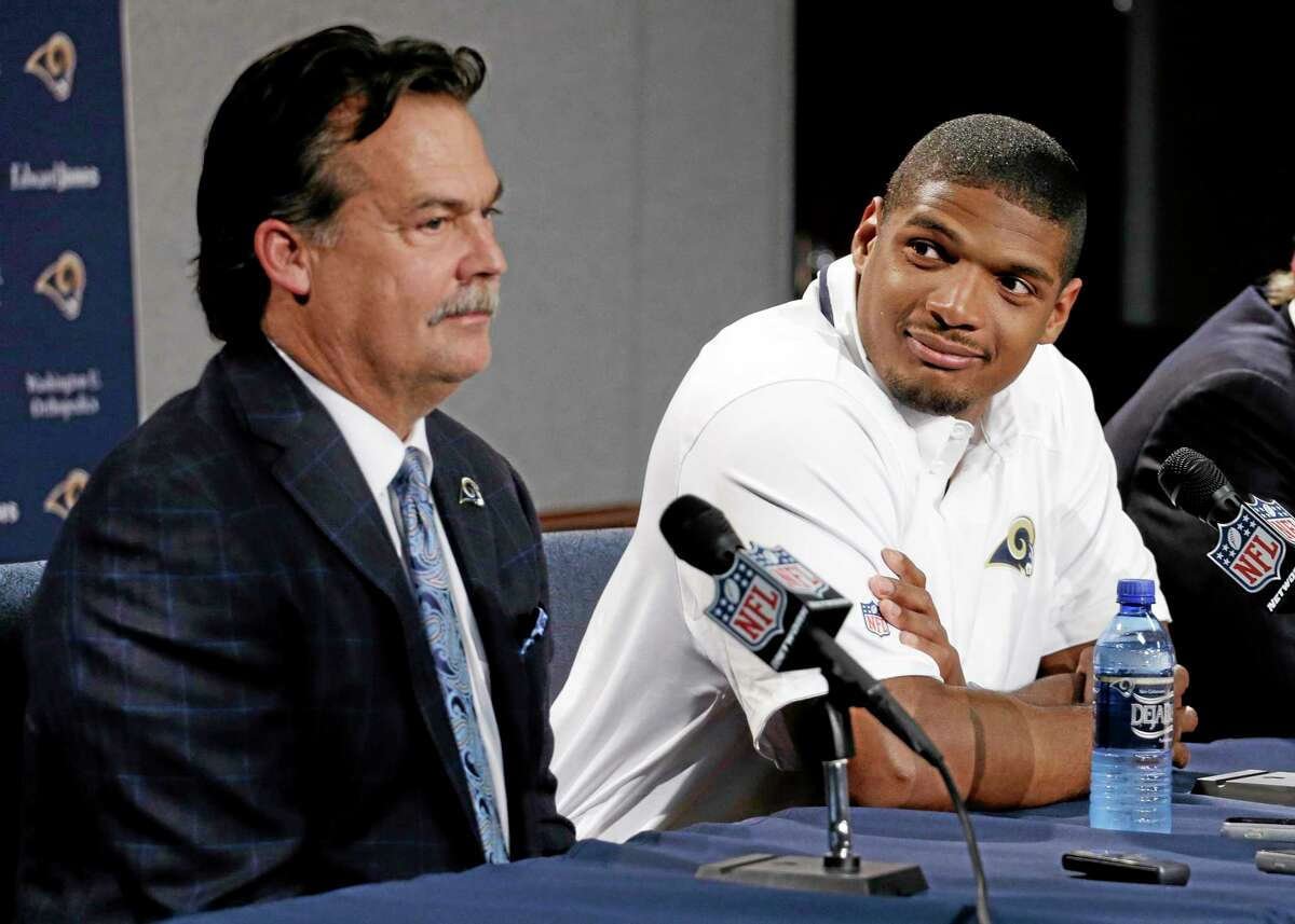 St. Louis Rams seventh-round draft pick Michael Sam, right, listens as coach Jeff Fisher speaks during a news conference on May 13.