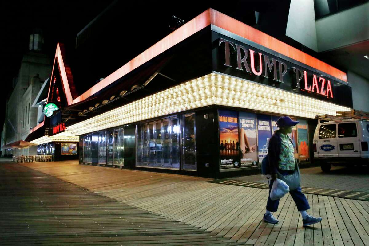 Burned out lights can be seen as a woman passes Trump Plaza Hotel & Casino on The Boardwalk early Tuesday, Sept. 16, 2014, in Atlantic City, N.J. Trump Plaza Hotel & Casino closed Tuesday. Trump Plaza is the fourth Atlantic City casino to go out of business so far this year.