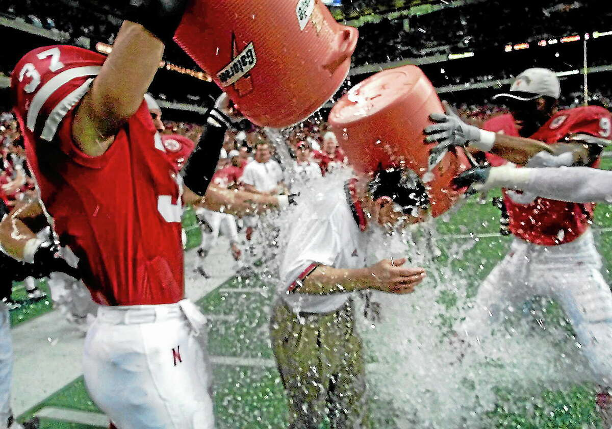 Eric Gay — The Associated Press Nebraska's Tony Ortiz (37) and Mark Vesral (9) dunk coach Frank Solich with water after the Huskers beat Texas 22-6 in the Big 12 Championship game in Dec. 4, 1999. Ortiz Sr. won two National Championships while playing at Nebraska.