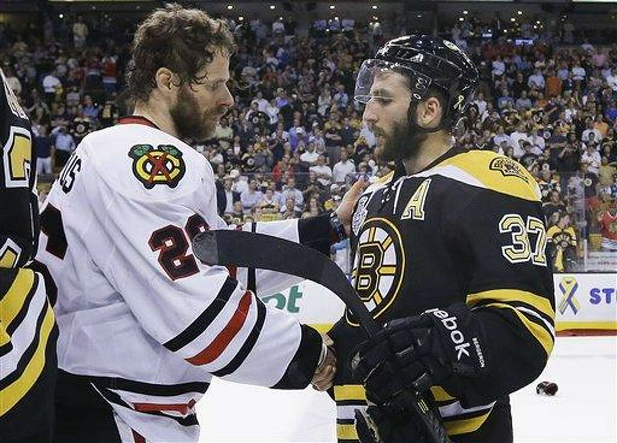 Chicago Blackhawks center Michal Handzus (26), of Slovakia, shakes hands with Boston Bruins center Patrice Bergeron (37) after the Blackhawks beat the Bruins 3-2 in Game 6 of the NHL hockey Stanley Cup Finals Monday, June 24, 2013, in Boston. (AP Photo/Elise Amendola)