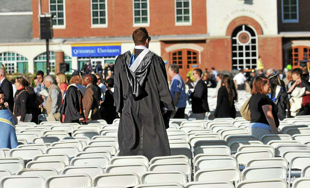 A Quinnipiac University graduate looks for relatives after the University officials decided to move the graduation ceremony from the main campus to the TD Bank Arena because of 'multiple security threats.' The main campus quad area, where the commencement was set to take place, was evacuated due to the threats. The university had two earlier graduation ceremonies during the day, without any problems. 5/18/14 pcasolino@newhavenregister.com